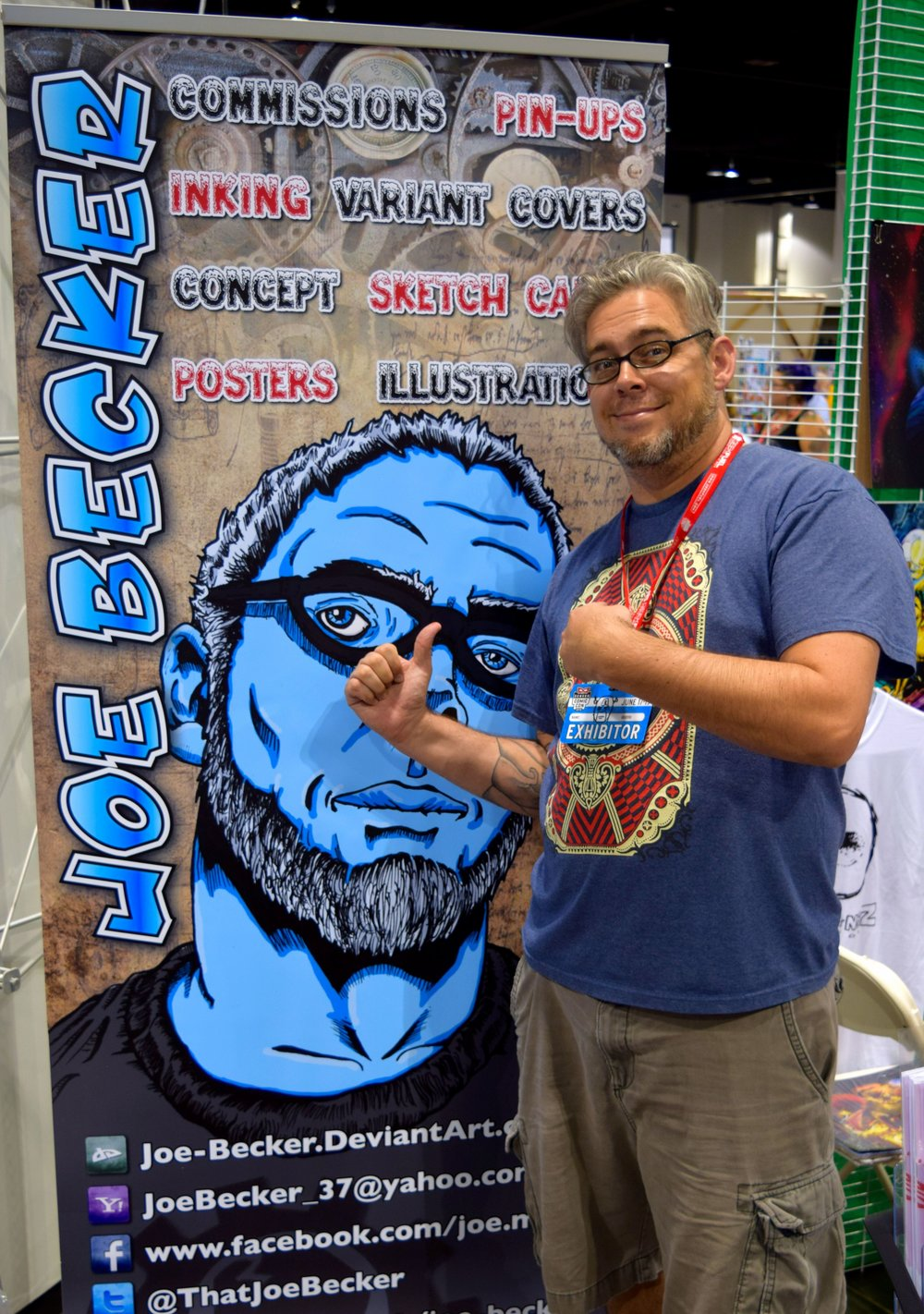 Joe Becker beside his banner at Denver Comic Con 2016.