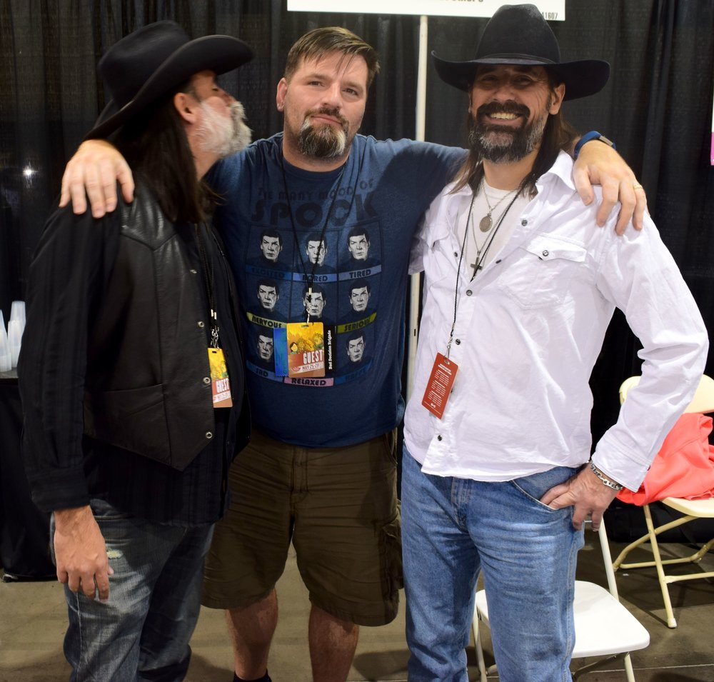 Matthew steals a kiss from author Mark Gardner while Shawn stands by at Phoenix Comic Con 2017.