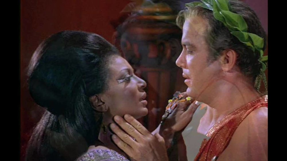 Lt. Uhura  and  Captain Kirk  share an embrace, and a kiss.