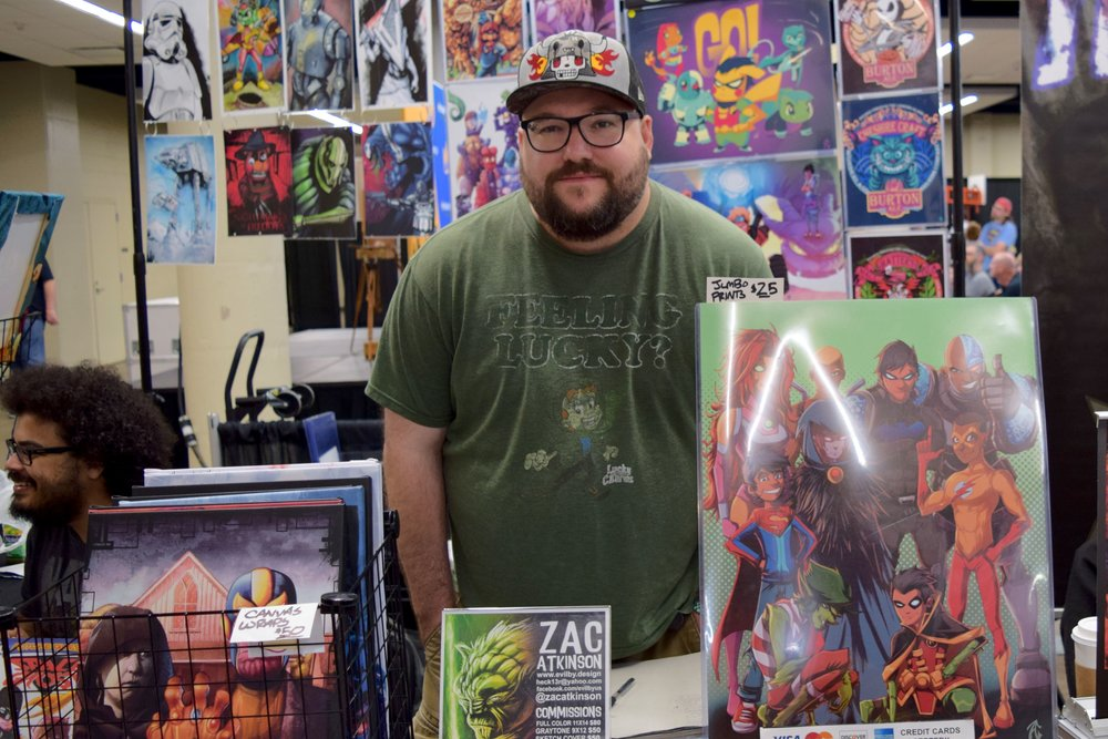 Zac Atkinson  standing with his art at WWDM 2018.
