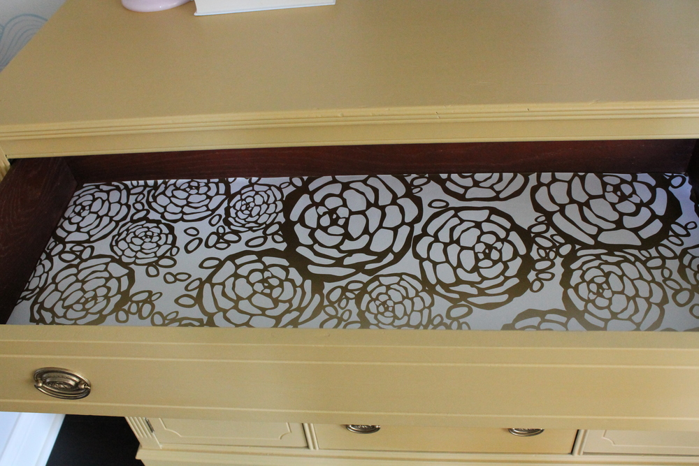 Oh Joy Wallpaper lining the drawers of this yellow sideboard