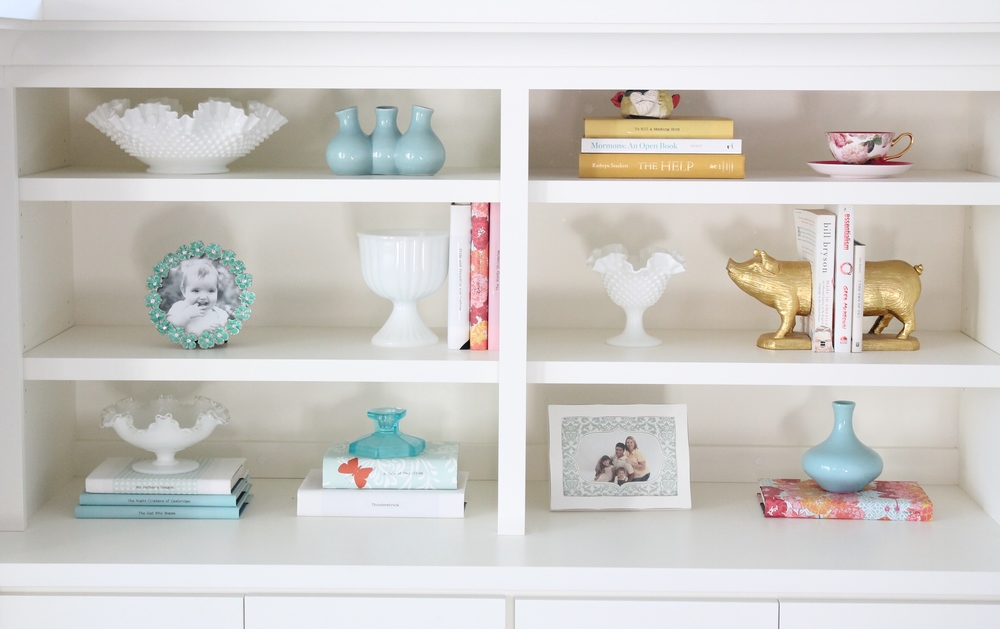 Built in bookshelf decorating ideas. Style a bookshelf with a cohesive color pallet by covering books with pretty paper. Add some glass objects and small frames to round out the design.