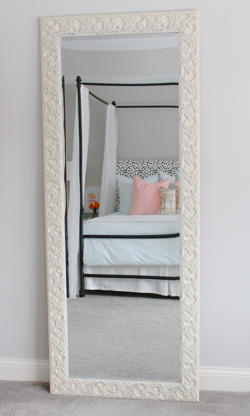 Lovely master bedroom with leaner mirror, pink and blue bedding and a dalmatian headboard.