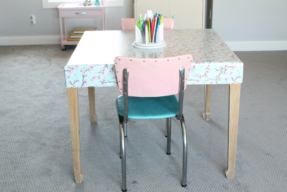 Kid's craft table covered in oilcloth with vintage school house chairs.