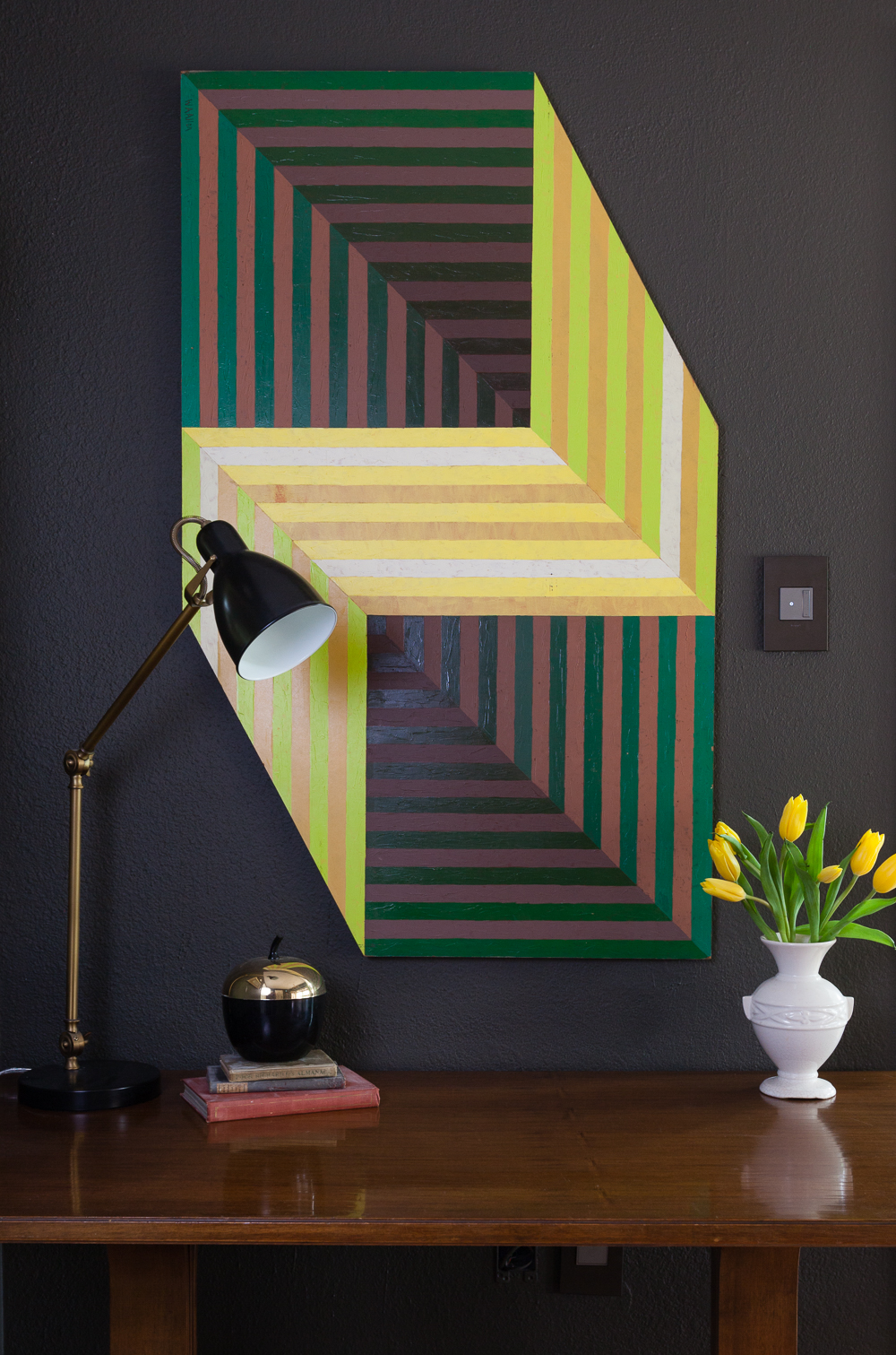 Benjamin Moore Dragons Breath paint with vintage 70s op art painting and switches by Legrand. Yellow tulips and brass West Elm lamp.