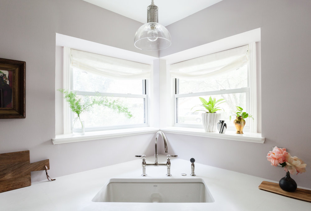 Farrow and Ball Peignoir paint with Kohler bridge faucet and relaxed roman shades by the shade store. Bright kitchen with caesarstone Fresh Concrete counters.