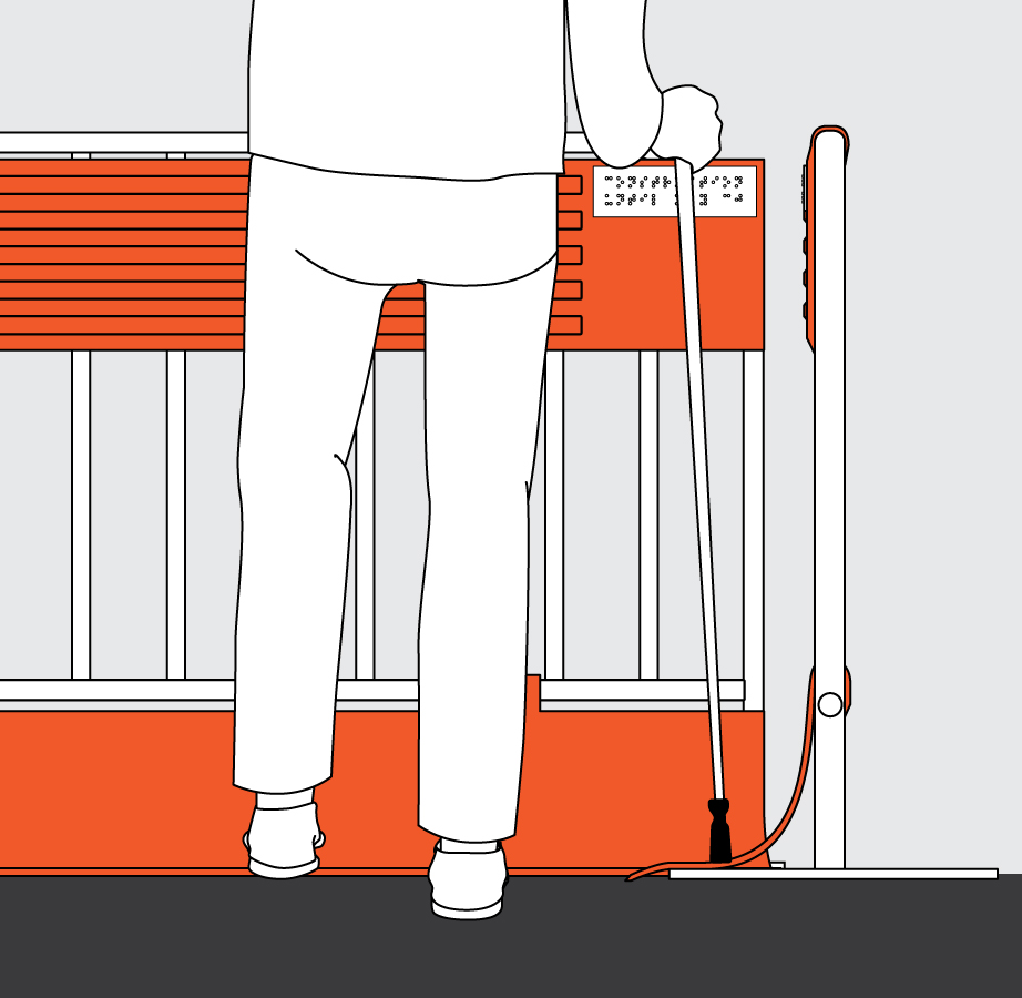 A pedestrian is using her mobility cane to touch the bottom guiding edge, which is attached to a construction barrier.