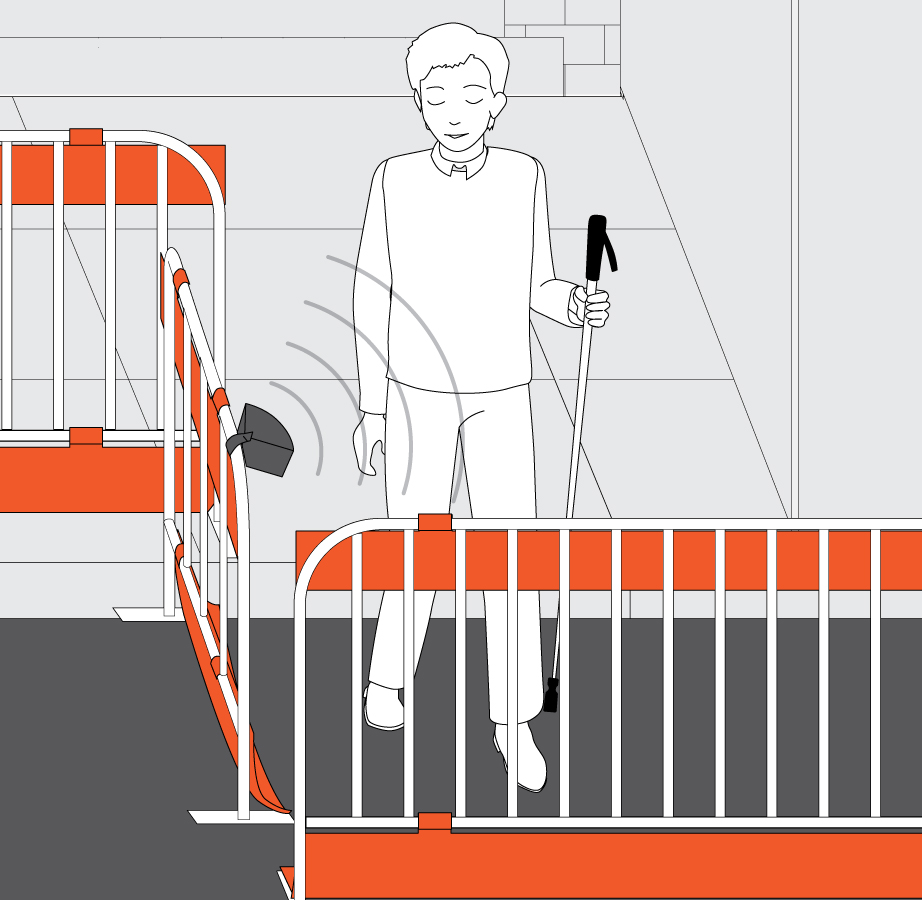 A speaker attached to the construction barriers is emitting sound which alerts the walking pedestrian that she needs to turn left.