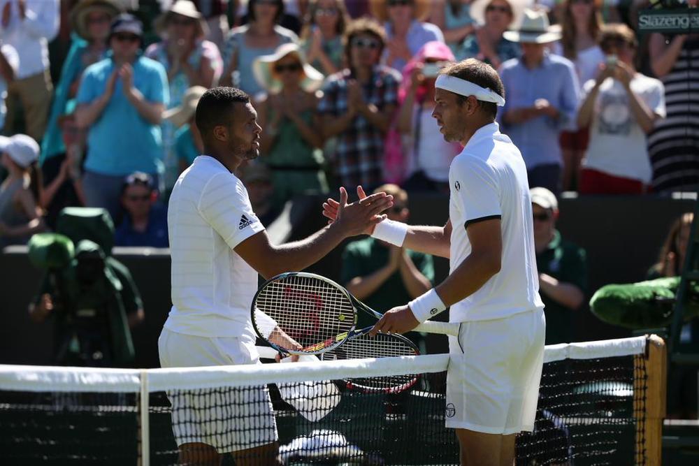 Jo-Wilfried Tsonga și Gilles Muller la finalul meciului lor de cinci seturi.