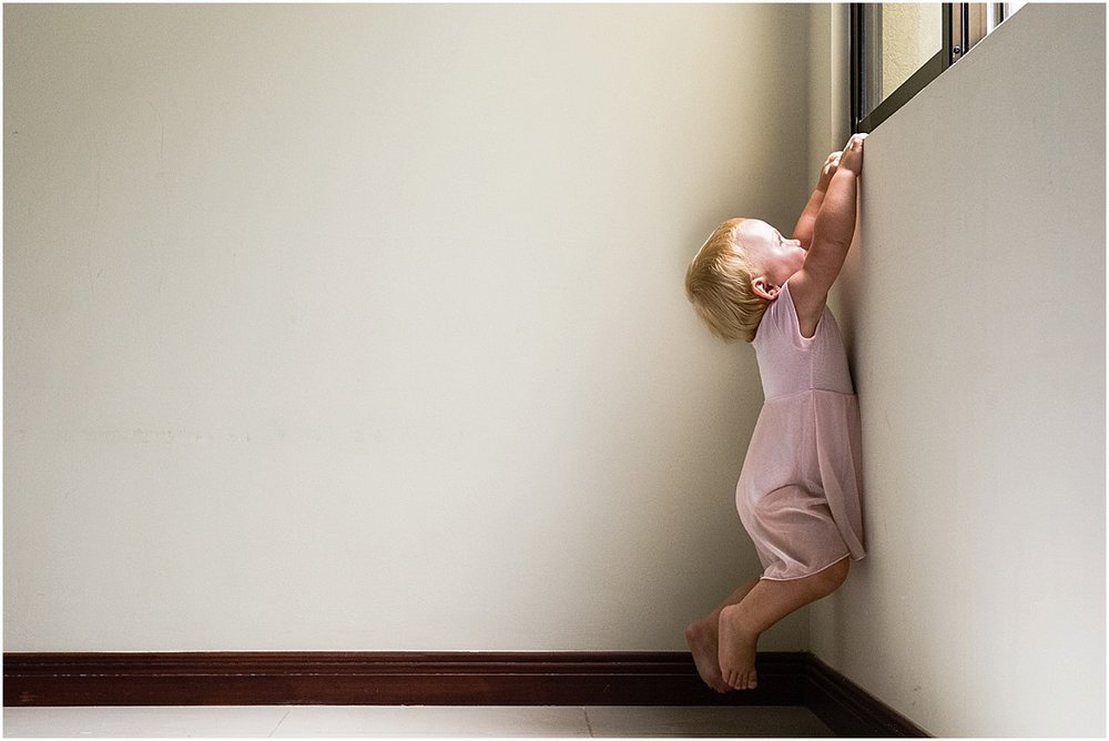 Ballerina baby climbing up a window in Costa Rica house