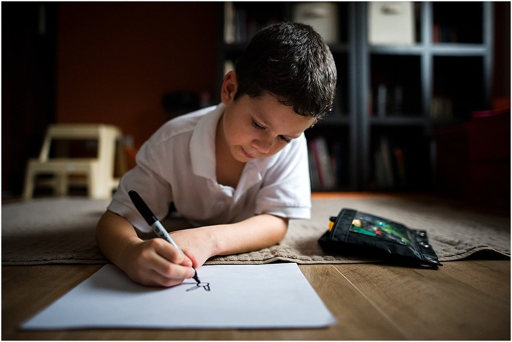boy drawing pictures on the floor during in-home lifestyle photography session in Costa Rica