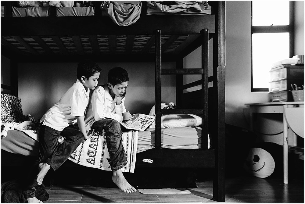 brothers reading on their bed during family documentary photo shoot in Santa Ana, Costa Rica