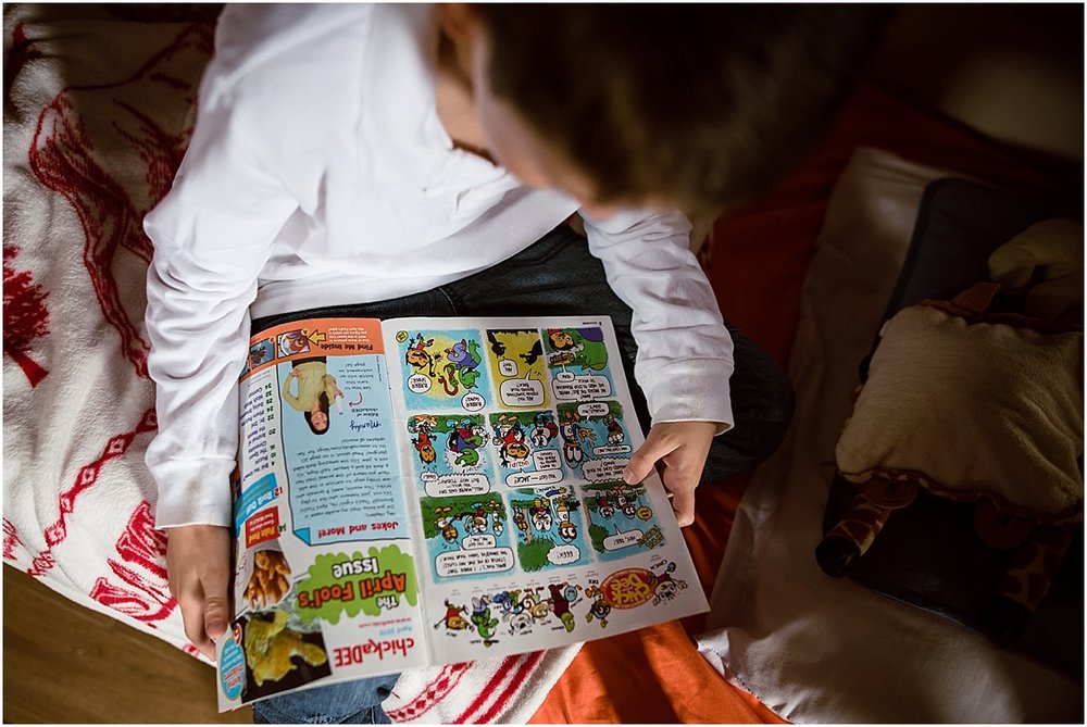 boy reading comics during in-home lifestyle photo session in Costa Rica