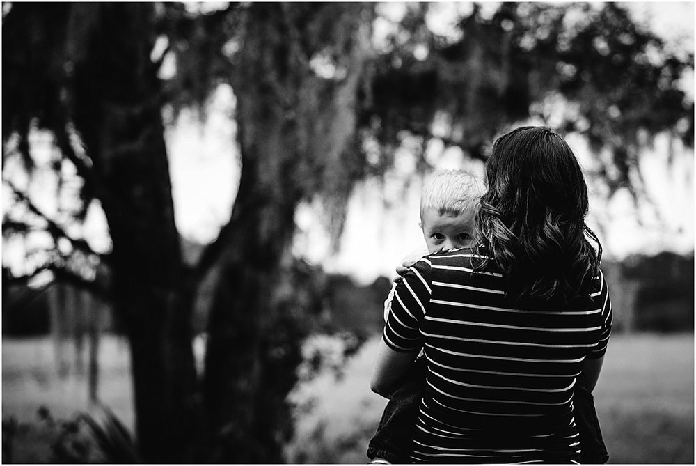 shy little boy hiding behind his mom for family pictures  | Oviedo Family Photographer