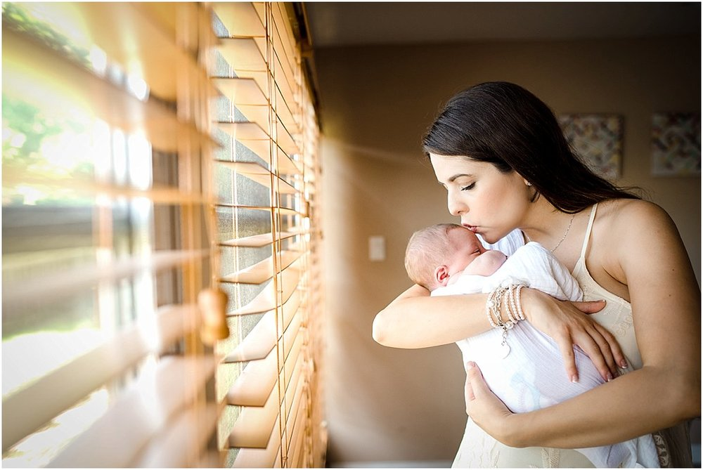 mom kissing her newborn baby boy during lifestyle newborn photography session