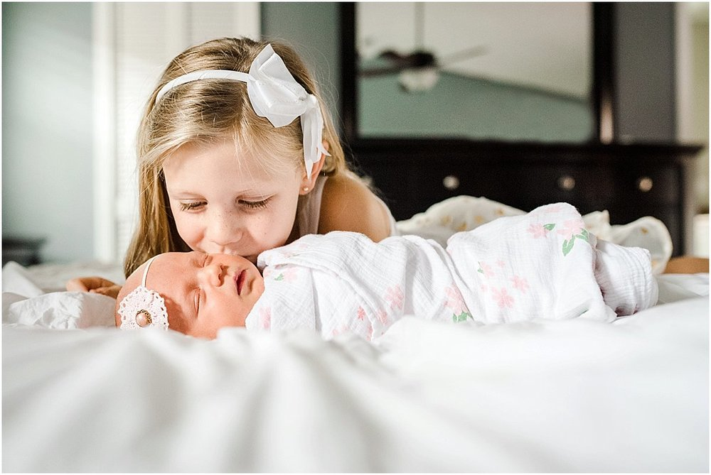 big sister kissing newborn baby sister