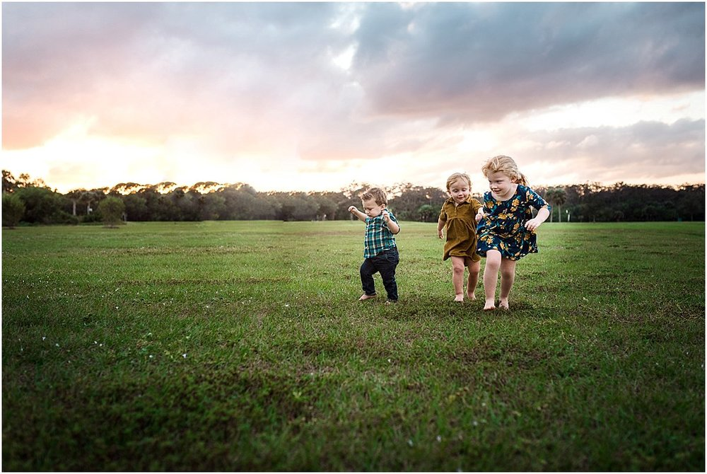 three cousins running in a field during family photoshoot