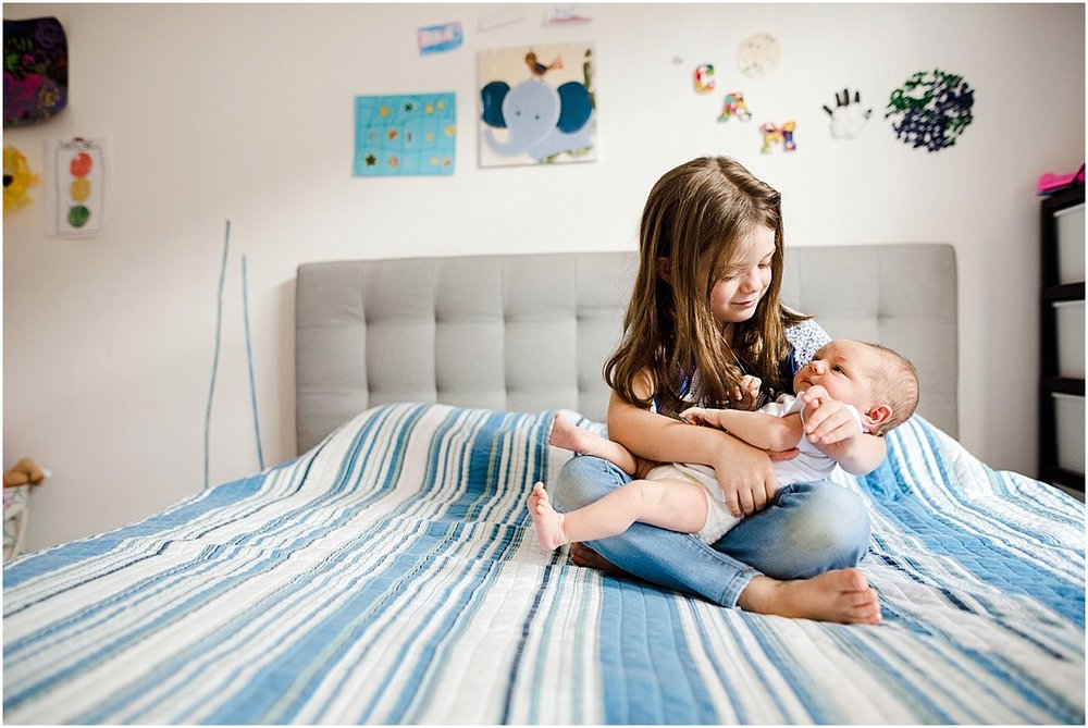 Big sister holding her brand new baby brother | Orlando lifestyle newborn photography
