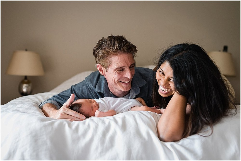 family laughing during in-home newborn photography session | Orlando newborn photographer
