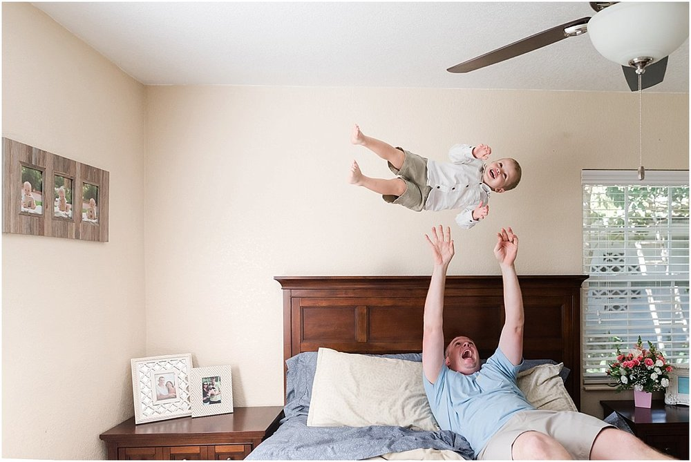 Dad throwing toddler son up in the air during in-home photo shoot | Orlando Family Photographer