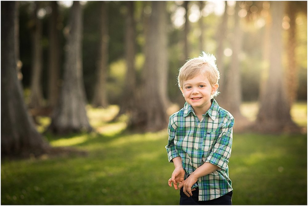 little boy giggling in the park during family photos