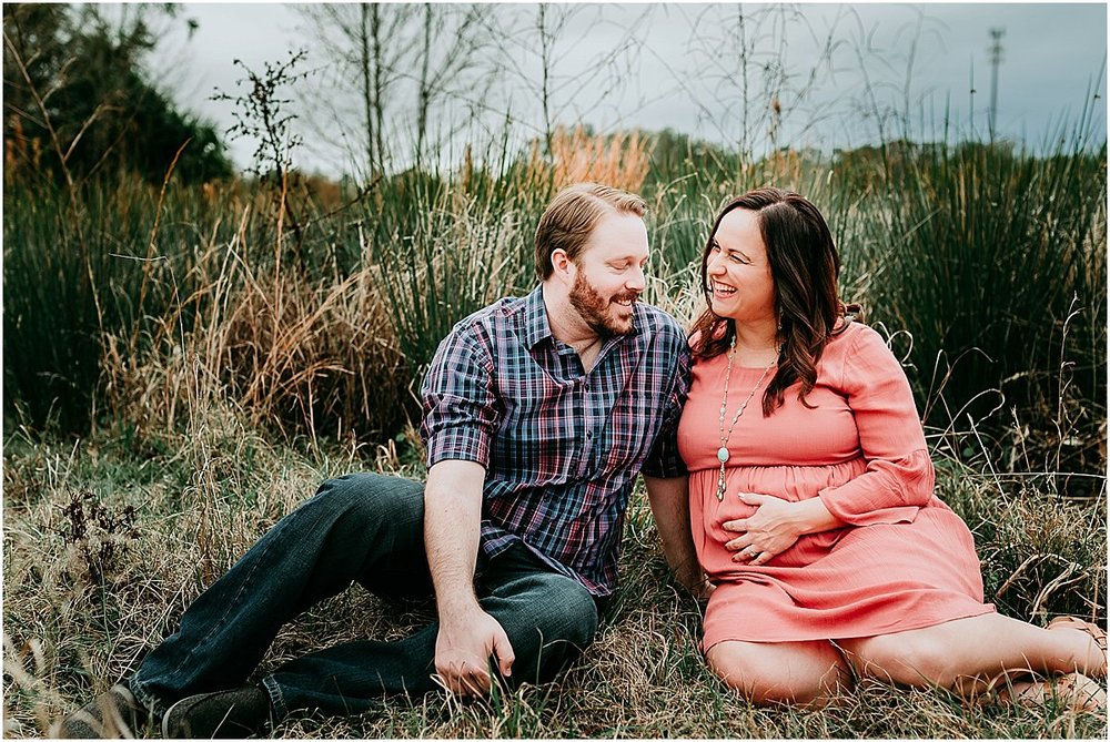 Pregnant mother with her hand on her belly and dad laughing | Orlando maternity photographer