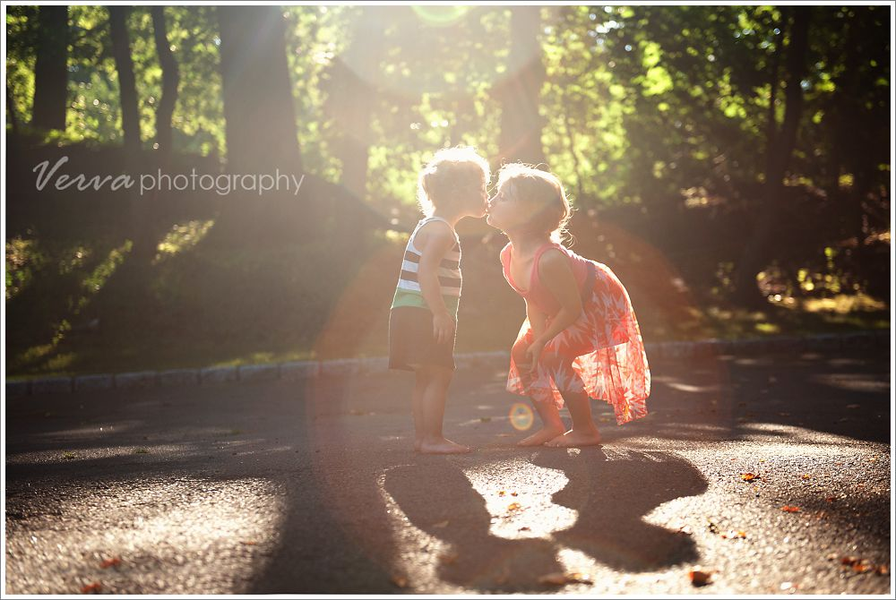 sisters kissing, sun flare children's portrait