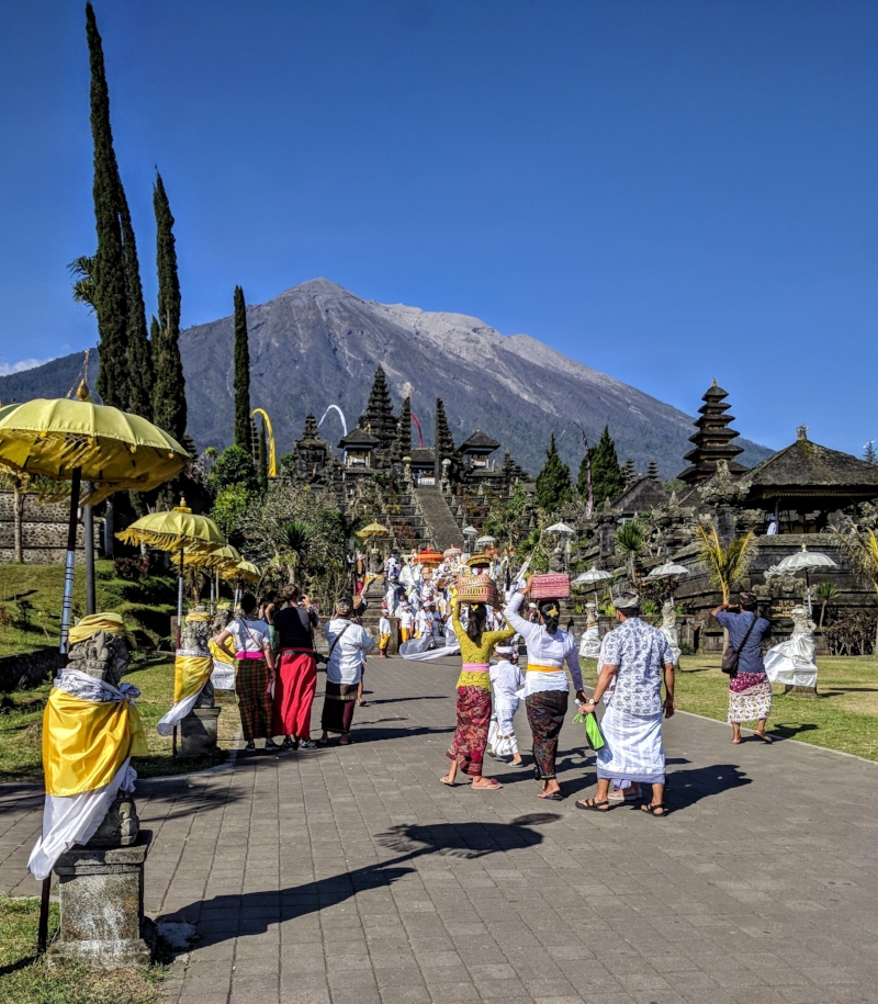 Walking up to Besakih Temple with Mt. Agung in the backdrop. The Balinese women (mostly) carry atop their heads, baskets filled with offerings (fruit, cakes, goods, flowers, incense, and the like) for their prayer rituals at the temple.