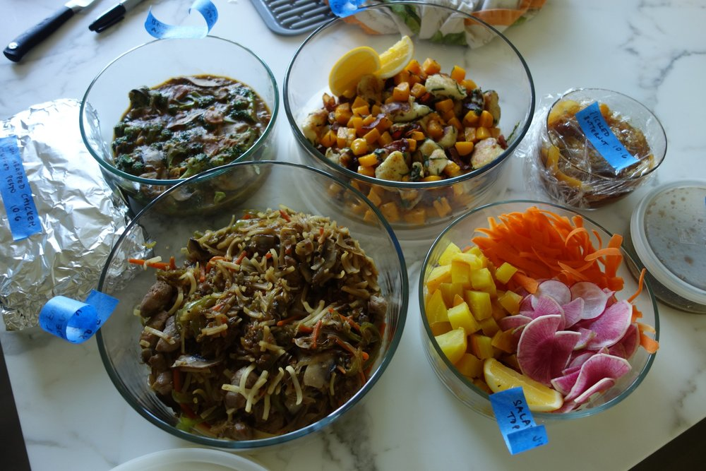The spread, including bacon wrapped chicken breasts stuffed with pesto, salad sides, balsamic vinaigrette, and pickled butternut squash