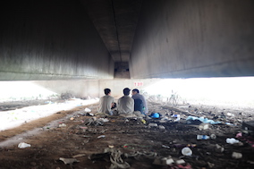 Blue Dragon social worker is chatting with children living under a bridge.JPG