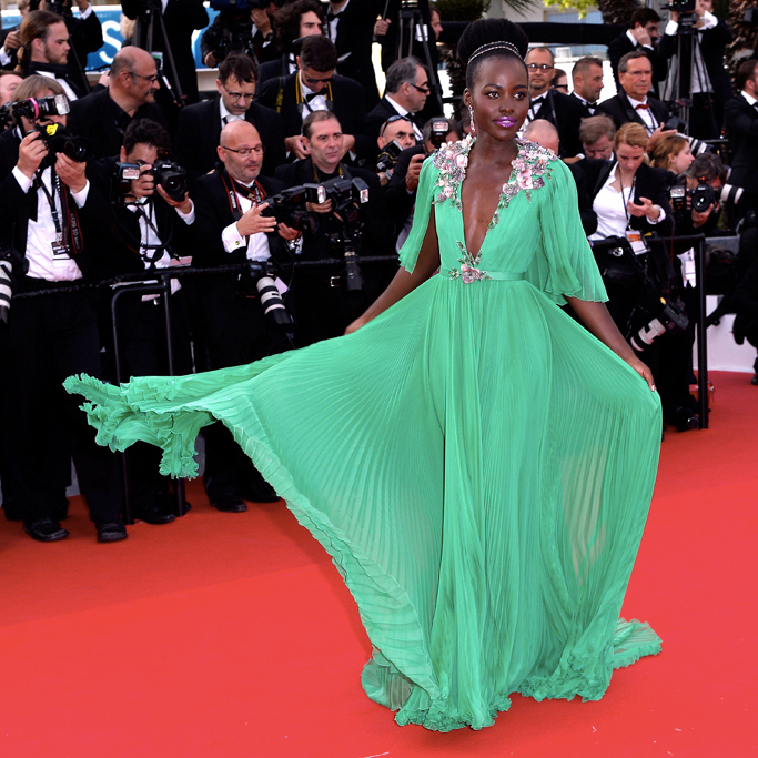"""wwd :       Cannes Opener Turns Into Ladies' Night     """"Among the other guests was Lupita Nyong'o, who playfully swished the skirt of her grasshopper green pleated Gucci gown for photographers""""    Read more about Cannes Opening Night on WWD.com    Photo by Pascal Le Segretain/Getty Images"""
