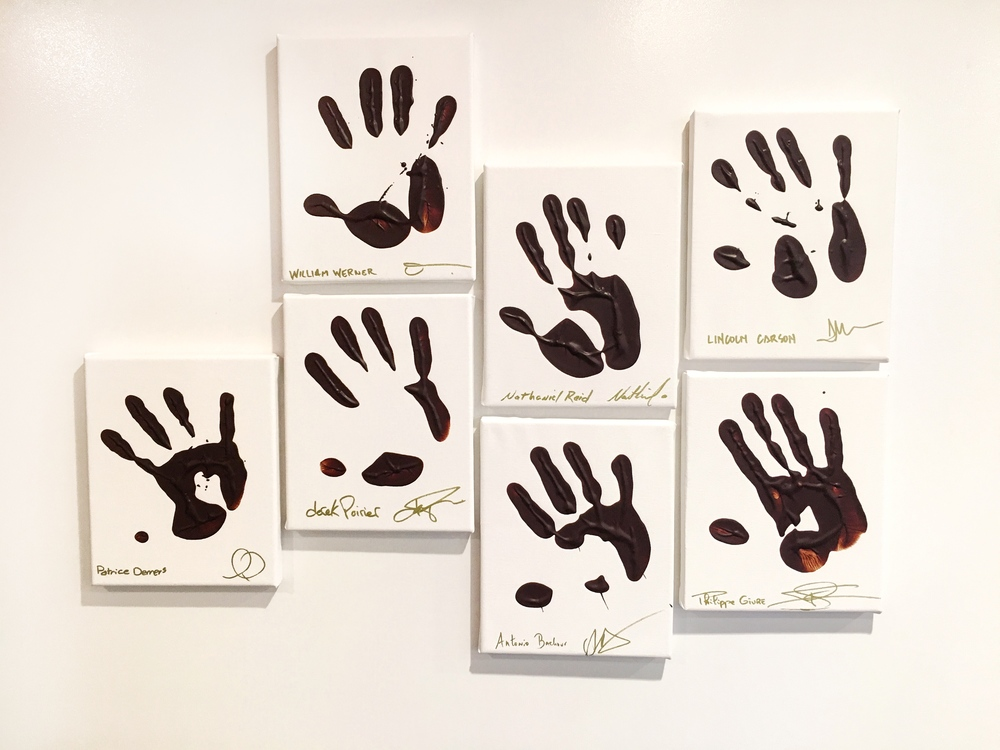 Famous chefs like Lincoln Carson with their hands dipped in chocolate, on the wall at Valrhona in Brooklyn