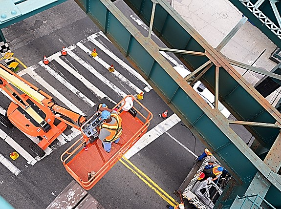 Proper fall protection and safe use of this articulating boom lift by a crew working on an elevated rail in New York City.