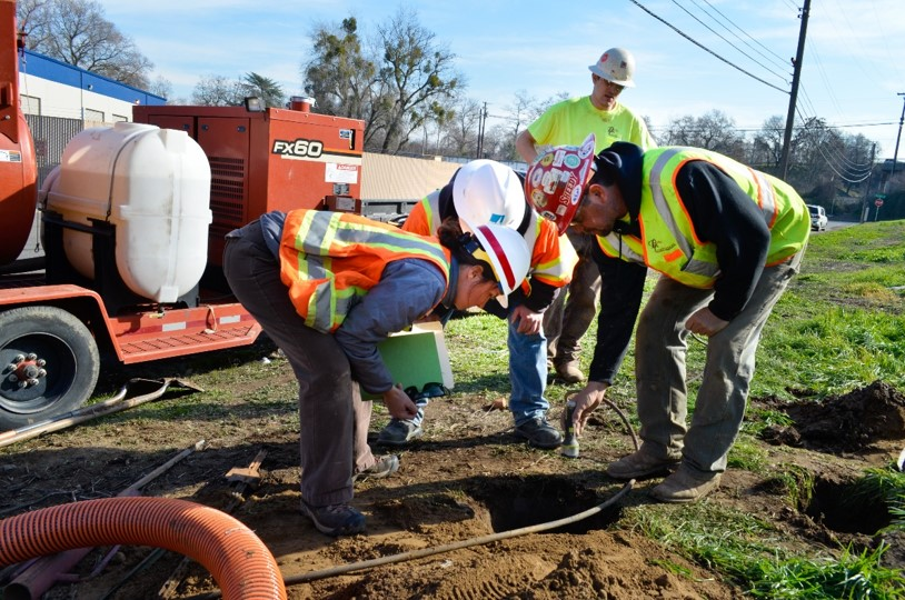Crew looks for a buried gas line in a freshly dug pot hole.