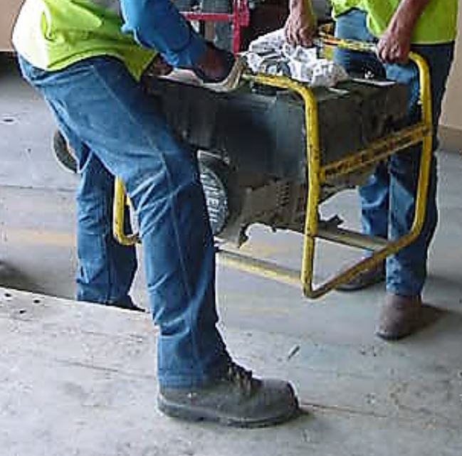 Workers lifting a heavy generator while wearing steel-toed work boots.