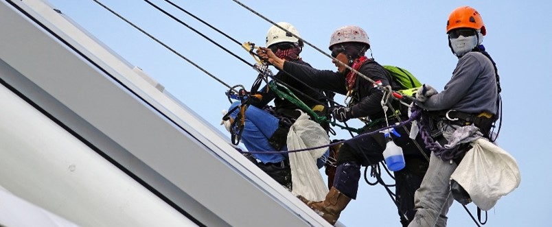 Workers using specialized climbing and fall protection equipment on a high pitched roof.