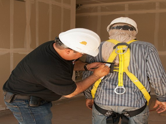 Supervisor documenting the completion of an inspection using the tag attached to the back of this full body harness.