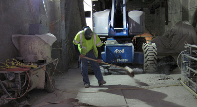 Worker sweeping up to ensure the job site stays neat.