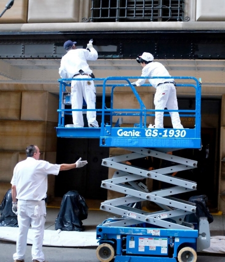 Workers using a scissor lift on the exterior of a building.