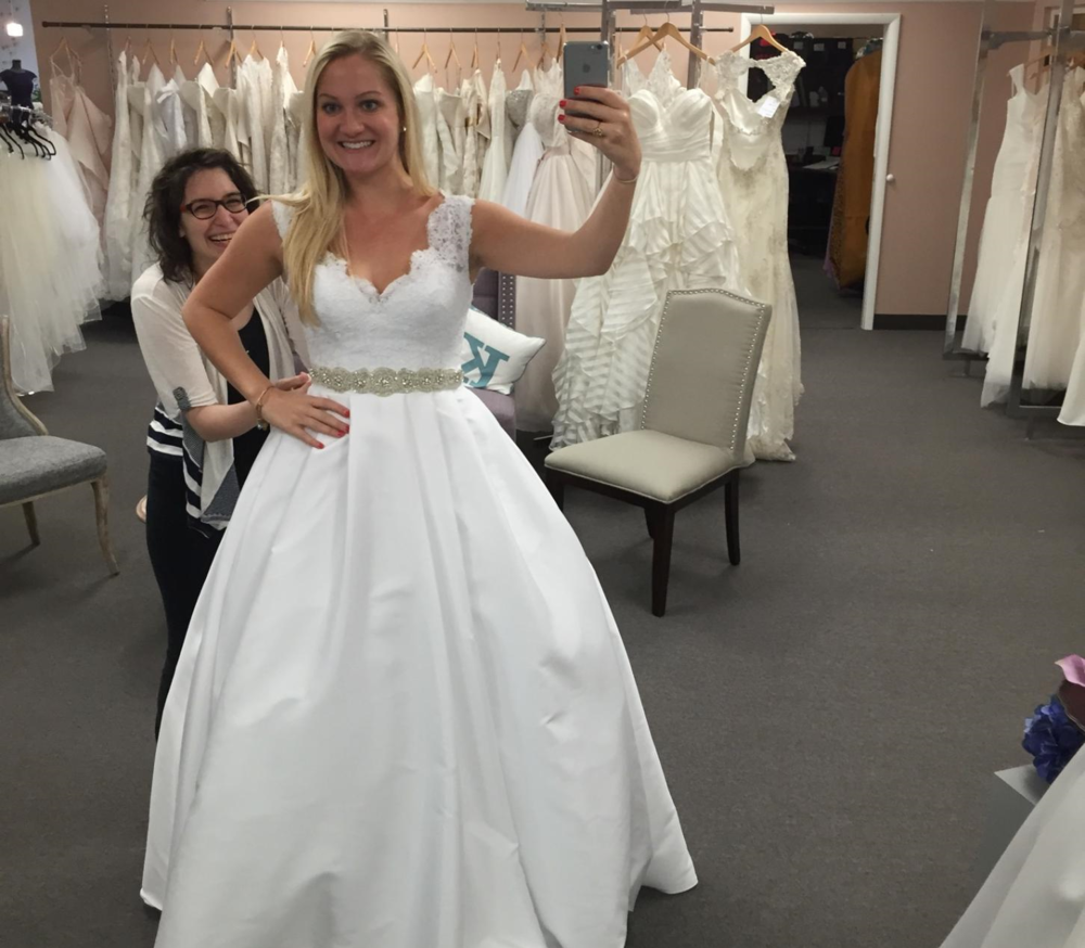 Bride-to-be trying on a dress with the help of a bridal consultant