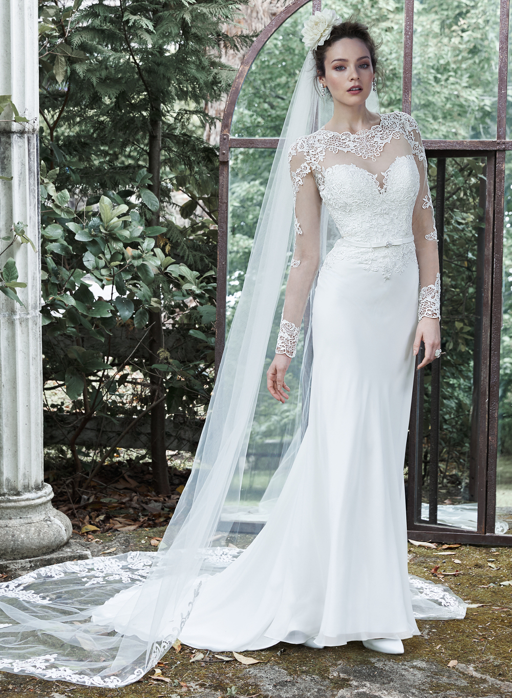 Vaughn -   This demure sheath dress gets an extra dose of drama with full-length illusion sleeves, neckline and illusion open back, edged with striking lace appliques. Romantic lace adorns the bodice before meeting a flowing Arlo chiffon skirt. Finished with delicate belt and covered buttons over zipper closure. Available with full-length tulle and lace veil. Detachable veil sold separately    Colors available - White, Ivory
