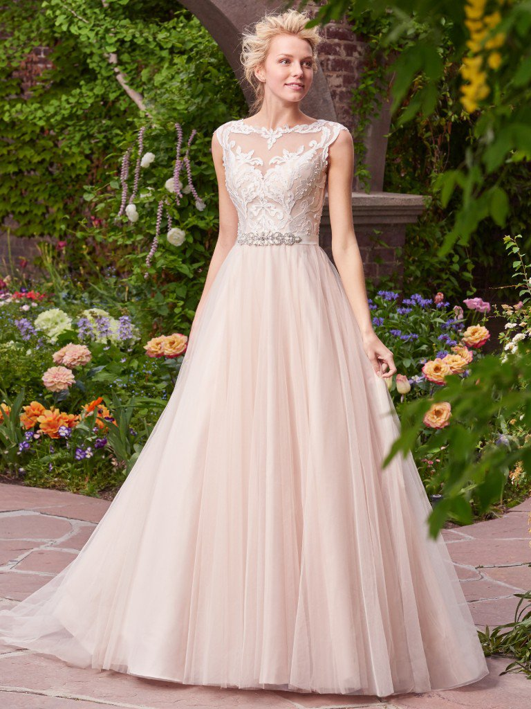 Carrie -  Charming and romantic, this tulle ballgown features lace appliqués that cascade over the bodice, illusion bateau neckline, and illusion back. Finished with covered buttons and zipper closure. Detachable beaded belt on grosgrain ribbon sold separately.  Colors available - White, Ivory, Ivory over Nude
