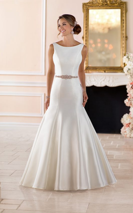 6369 -  This boat neck wedding dress with deep-v back by Stella York is a modern masterpiece! Made exclusively in Grand Mikado fabric in a gorgeous trumpet silhouette, this elegant wedding dress will make a statement at your wedding. The clean lines come together to create a high neckline that swopes into a deep-v back and flows into a long, stunning train. The ornate belt adds to the glam factor with gold accents of Diamante. Fabric covered buttons start where the back ends and trail down the train for even more simplistic drama. This wedding dress is also available in plus sizes.  Colors Available - Ivory, White