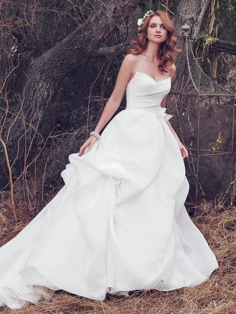 Meredith -  This simple yet glamorous Cameo Organza ballgown features a softly pleated bodice and voluminous pickups in the skirt. A distinctive sweetheart neckline and handmade 3D floral motif, accented with Swarovski crystals, at the hip and skirt add unique romance to this wedding dress. Finished with zipper closure.  Colors Available - Ivory
