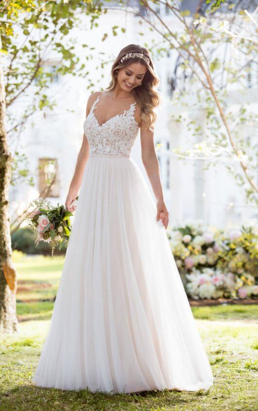 6555 -  Soft, romantic, and light-as-air, this boho wedding dress from Stella York was made for the laidback, casually-cool bride. The bodice of this French tulle over matte-side Lavish satin gown is constructed of double organza, giving the appearance of sheerness. Adorned with lace swirls and beading, it is the perfect complement to the tulle, A-line skirt. The back of this gown features an intricately-detailed illusion-tulle design, and a slight train, making it perfect for a boho-inspired celebration. This boho wedding dress zips up beneath pearl buttons.  Colors Available - All Ivory, Ivory/Moscato/Mink, All White
