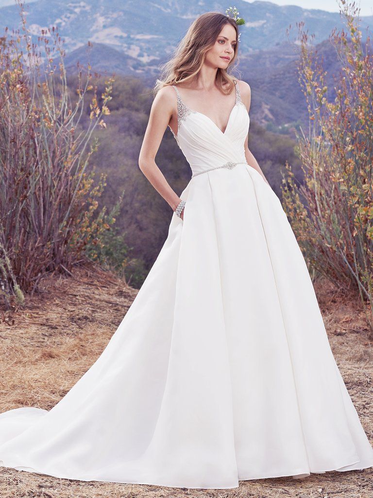 Rory -  This Shavon Organza ballgown features an asymmetrically pleated bodice and soft pleats in the skirt. Beaded straps glide from the deep V-neckline to a V-back trimmed in beaded illusion. A dazzling bead and Swarovski crystal belt completes the unique romance of this wedding dress. Finished with covered buttons over zipper closure.  Colors Available - White, Ivory