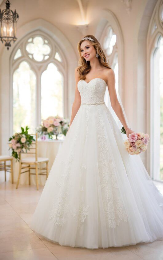6461 -  Bring your dream fairytale wedding day to life with this ballgown from Stella York! With a subtle sweetheart neckline, the lace bodice of this lace, tulle and Regency organza over satin gown frames the face and adds an air of elegance to this princess style. A detachable, beaded belt accentuates your waist before flowing gracefully into a full, ballgown skirt – the feature of this gown that truly sets it apart from other princess wedding dresses. Re-embroidered soft lace creates an incredible linear pattern on the skirt, giving it an ornate look that extends through the small train. This gown has the option of a lace-up back or zip up beneath fabric buttons and is available in plus sizes.  Colors Available - White, Ivory, Ivory/Moscato
