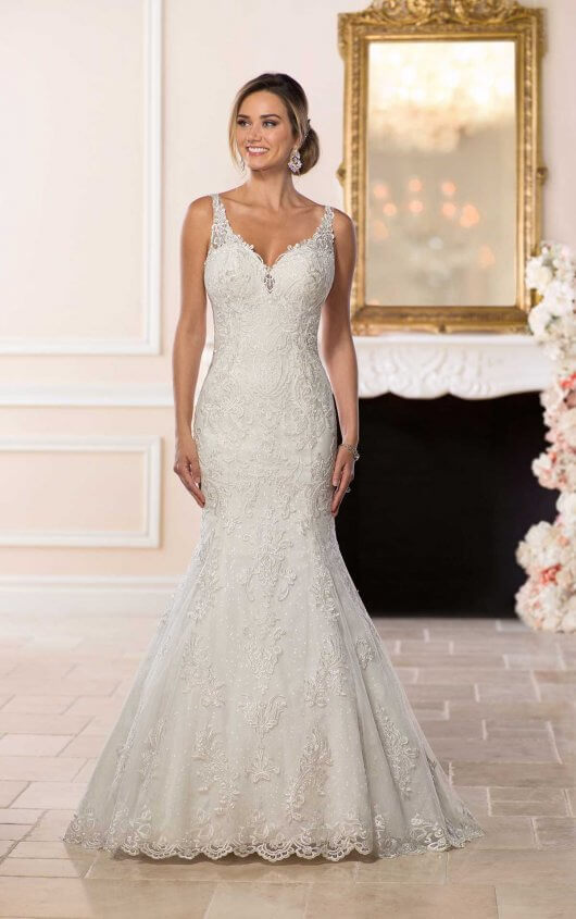6571 -  So very sparkly and undeniably sexy, this wedding dress by designer Stella York is simply a masterpiece! Layers of lace and tulle create a slim, modern fit-and-flare shape that flares out just below the hips for a dramatic finish. The full skirt comes with the option of matte tulle or sparkling sequin tulle for even more glamour. Deep, sheer side cutouts meet at an open back, which mirrors the plunging V-neckline. The layered floral lace fabrics create movement and drama throughout the bodice and cathedral-length train, which is finished with a magnificent full lace hemline. By adding beading throughout the gown, the subtle details of the lace shine and are given an extra pop! This stunning wedding dress zips up under buttons and is also available in plus sizes.  Colors Available - White, Ivory