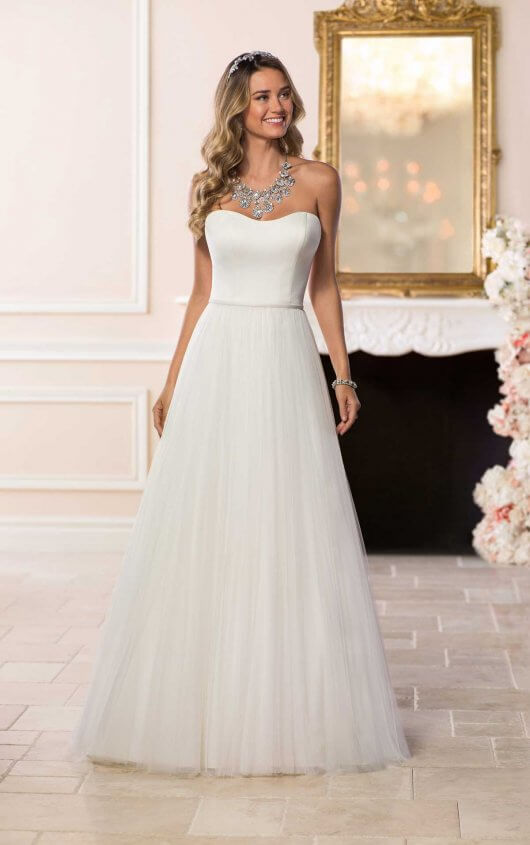 6594 - Simple, classic and perfect for adding the right accessories, this designer wedding dress by Stella York was made for a fun and flirty bride! Style this tulle and crepe A-line wedding dress with a jeweled belt or long veil for a vintage touch. The soft sweetheart neckline dips modestly and creates a very flattering shape to the bodice. A detachable belt defines the waistline where a tulle A-line skirt flows out giving off a dreamy, bridal effect. A chapel-length, tulle train finishes the skirt with grace. This simple and vintage-inspired wedding dress is both affordable and fashion-forward with the ability to style any way you want! Available in plus sizes, this wedding dress closes with buttons over a zipper.  Colors Available - White, Ivory