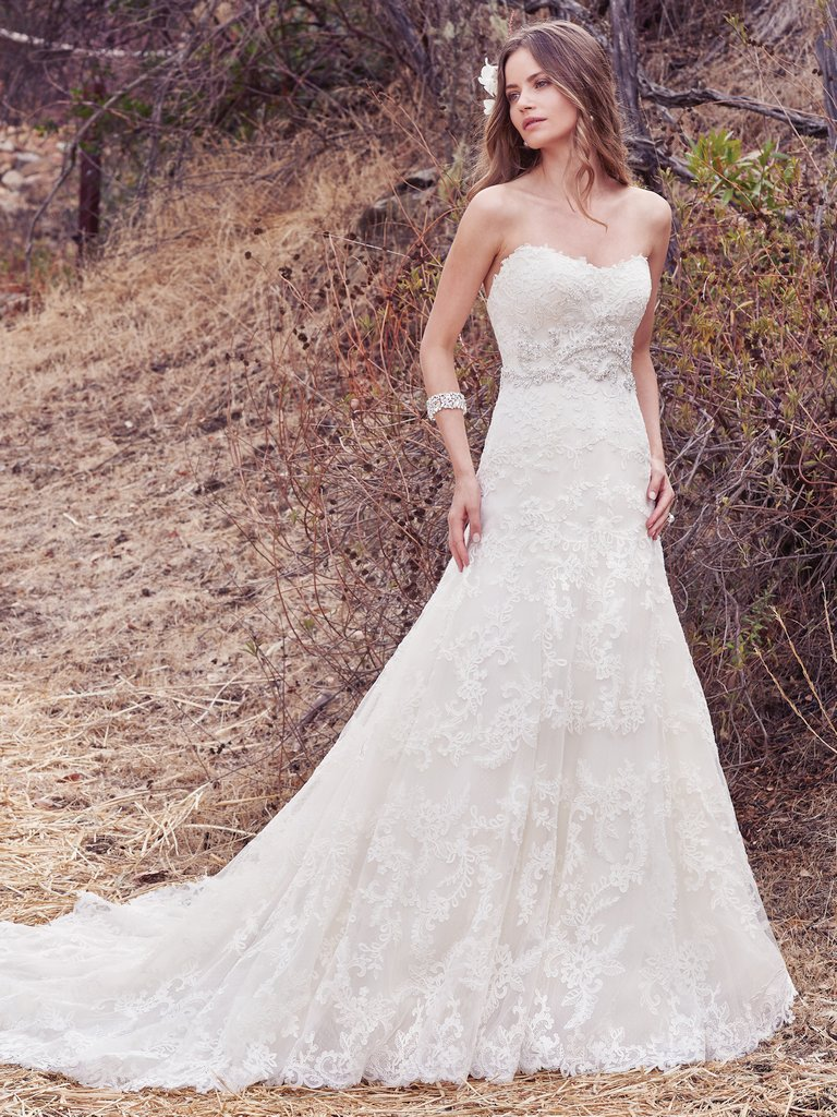 Genoa -  Classic and romantic, this lace A-line wedding dress features a bead and Swarovski crystal motif at the waist. Complete with soft scoop neckline and soft V-back. Finished with crystal buttons over zipper closure.  Colors Available - Ivory/Light Gold